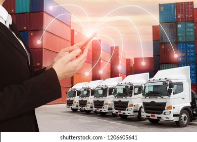 People using Mobile phone and illustration connectivity to control truck fleet GPS with container depot shipping industry logistics background.