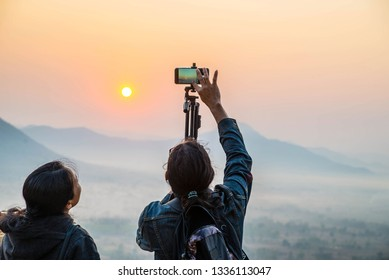 People using smart phones to take pictures of the sunrise in the morning.