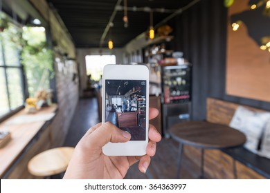 People using smartphone take a photo in coffee shop. Coffee shop is a most popular place to check in and take a photo to social networks