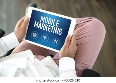 People using tablet pc and MOBILE MARKETING concept on screen