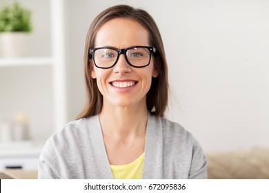 people and vision concept - happy smiling middle aged woman in glasses at home