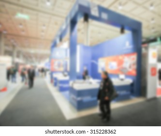 People visit a fair, generic event background, intentionally blurred post production.