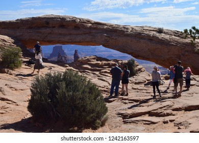 People visit the legendary scenic Mesa arch on of the Natural Rock Arches in Canyonlands National Park