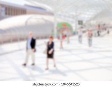 People visit a trade show. Background with an intentional blur effect applied.
