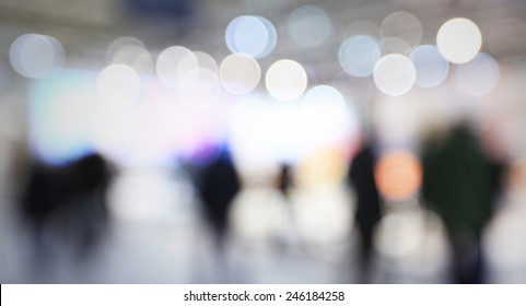 People visit a trade show, generic background, humans and location not recognizable. Intentionally blurred post production.