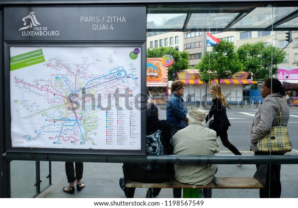 People wait for the bus at the bus stop in LUxembourg on Jun. 22, 2018