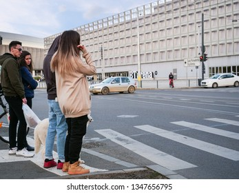 People wait on the sidewalk at the zebra crossing for the traffic light in Cluj-Napoca, Romania, March 23, 2019