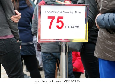 People waiting in a long queue, focus on the information sign. Billboard with information about the time waiting beside line with many people waiting.