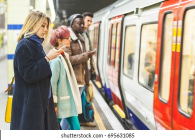 People waiting for the train at subway station. Mixed race persons, two men and two women, staying on a line and waiting to board the train. Commuting and transport