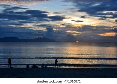 People walk along the beach of Nha Trang in Vietnam at dawn