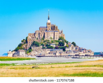 People walk along a causeway to reach the historic Le Mont-Saint-Michel, Normandy, France, on a bright summer day.l