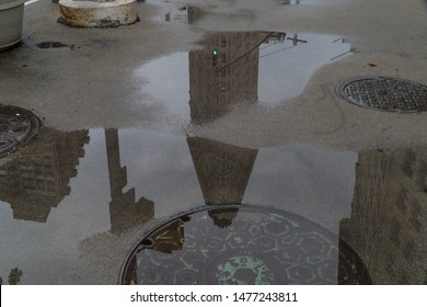 People walk during morning rush hour along side walk with generic buildings skyline reflection in rain puddle looking to stormy sky in water