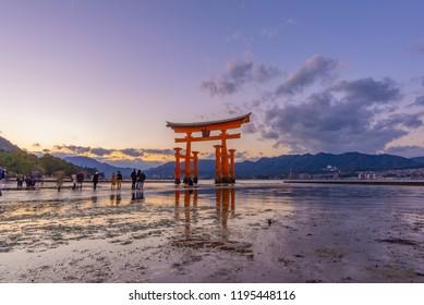 People walk to Itsukushima Big Red Floating Torii Gate when the sea was down with beautiful sunset color sky at Miyajima Island, Hirosihma, Japan Nov 23, 2017