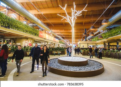 people walk in modern interiors supermarket next to a white illuminated bare tree in Fico Eataly World in Bologna, Italy, 19 Nov 2017