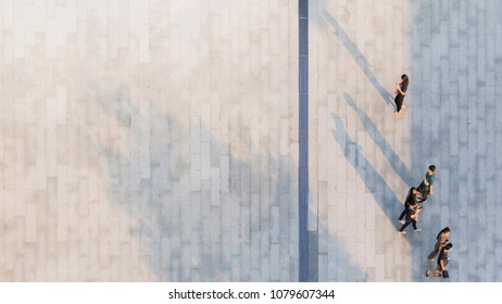 people walk on across the pedestrian concrete landscape with black silhouette shadow on ground (top aerial view)