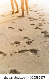 people walk on the beach with foot print behind
