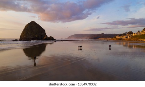 People walk on the beach reflection late afternoon at dusk in Cannon Beach Oregon