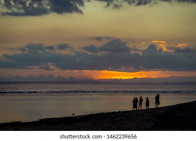 People walk on the ocean against the background of an incredible sunset. Mauritius, Indian Ocean