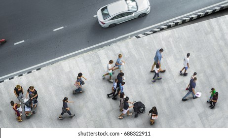 people walk on the pedestrian street walkway with the teenage young man and the group of family with little child with road and car transport. (Aerial urban city photo)