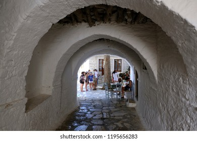 People walk on the typical cycladic, whitewashed alleys at Apeiranthos village on the island of Naxos, Cyclades, Greece on Aug. 18, 2018
