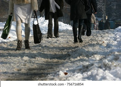 People walk on a very snowy sidewalk. People step on an icy pathway, icy sidewalk