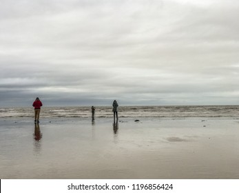 People walk out on the beach during the day of rain