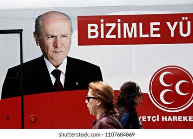 People walk past of a poster of Nationalist Movement Party election campaign in Istanbul June 2, 2015
