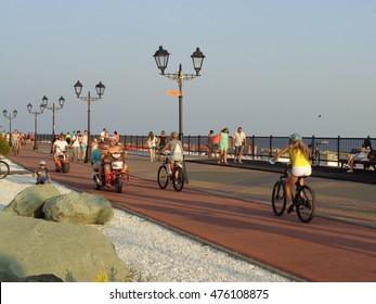 People walk and ride bicycles on the seaside promenade, resort Sochi, Russia, August 4, 2016