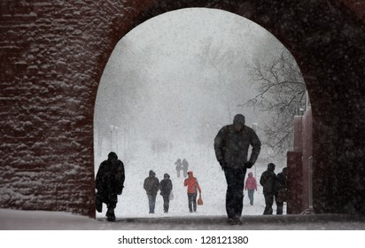 People walk in a snowfall in a park