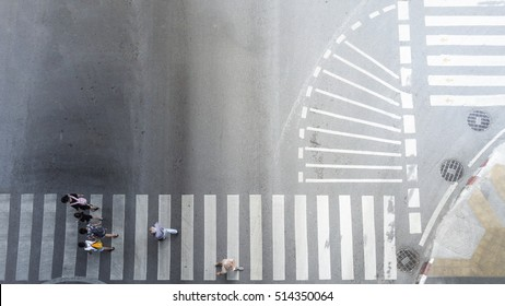 people walk through the crosswalk in the business road with other sinage on the background (Aerial city photo, top view)