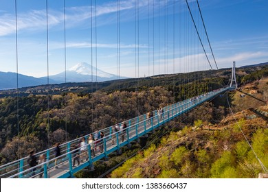 People walkin on Mishima Skywalk bridge with Mount fuji seen in the distant, clear sunny day