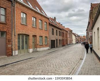 People Walking Along a Cobblestone Street in Bruges