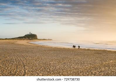 People walking along Nobby's Beach at Sunrise, Newcastle, Australia