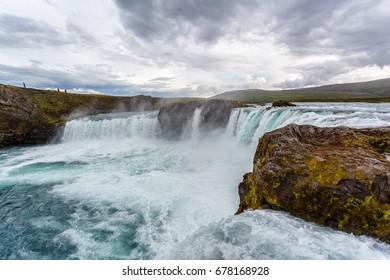 People walking around Godafoss waterfall in Iceland