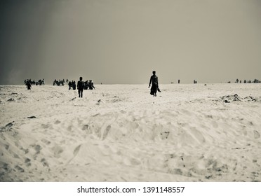 People walking around a sandy coastal area black and white photo