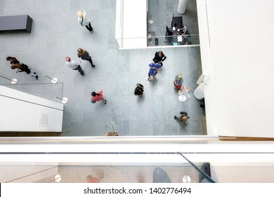 People walking around in the visitor hall room from top view at MoMA museum of modern art New York, USA on 18 May 2019