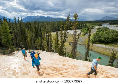 People walking barefoot through the Tufa Mounds in the Northwest Territories, Canada.
