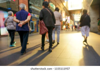 People walking in a bright, warm color shopping mall. Blurred image of a shopping center.
