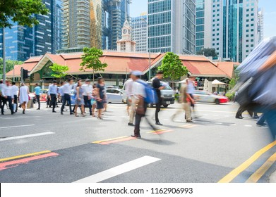 People walking by crossroad during rush hour in business center of Singapore
