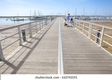 People walking by footbridge at Marina of El Rompido, Cartaya, Huelva, Spain