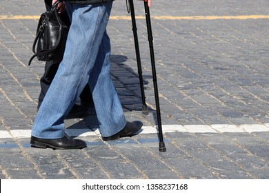 People walking with cane on a street. Two men on the sidewalk, concept for disability, old age, limping person