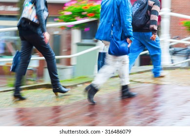 people walking in the city on a rainy day in motion blur