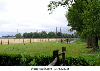 People walking in the countryside near Tilburg, North Brabant, The Netherlands with the towers of Koningshoeven Abbey a monastery of the Trappists (1881) in the background