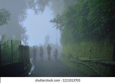 People walking in dark foggy road in Darjeeling.