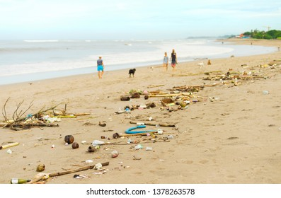 People walking with the dogs by polluted with plastic and waste beach. Bali island, Indonesia