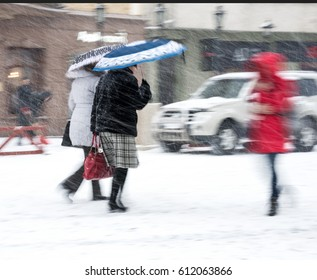 People walking down the street in a snowy winter day in motion blur
