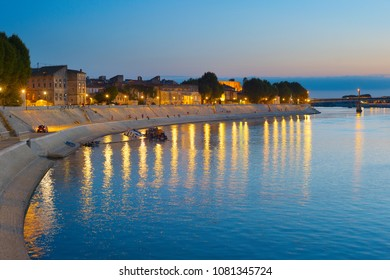 People walking at an embankment of Arles, France at twilight