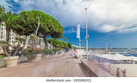 People walking at embankment near famous La Croisette Boulevard timelapse hyperlapse. French Riviera. Green trees, blue cloudy sky at summer day