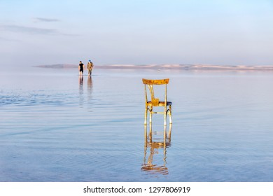 The people is walking in the Lake Tuz (Turkish: Tuz Golu) and a chair. Lake Tuz was declared a specially protected area, including all of the lake surface and surrounding waterbeds.
