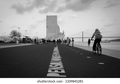 People walking in Lisbon with the Monument to the Discoveries in background. Lisbon, Portugal March 2019